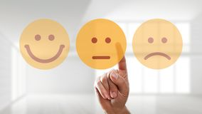 Hand is selecting a neutral mood smiley. In front of an empty room royalty free stock images