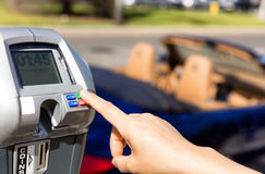 Hand selecting time on parking meter with convertible car in bac Stock Photos