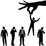 Hand selects business man silhouette group. A female hand to find, select, choose, pick a business man to dangle above a line of business people Stock Photo