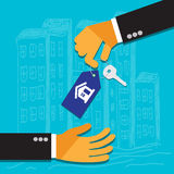 Hand of the seller holds key for house and gives it to buyer Stock Photos