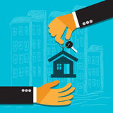 Hand of the seller holds key for house and gives it to buyer Royalty Free Stock Images