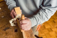 Hand of a senior carpenter with wood planer stock photo