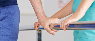 Hand of senior man on handle of treadmill Stock Image