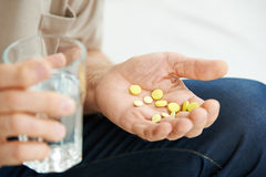 Hand of senior man with pills and water Stock Images