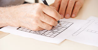 Hand of senior man solving sudoku Royalty Free Stock Images
