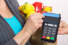Hand of senior woman using payment terminal with contactless credit card, paying for shopping Stock Photography
