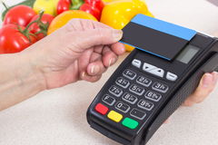 Hand of senior woman using payment terminal with contactless credit card, paying for shopping Royalty Free Stock Photos