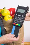 Hand of senior woman using payment terminal with credit card, cashless paying for shopping. Fruits and vegetables in shopping bag Royalty Free Stock Photography