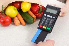 Hand of senior woman using payment terminal with credit card, cashless paying for shopping. Fruits and vegetables Stock Photo