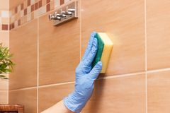 Hand of senior woman wiping bathroom tiles using sponge, household duties concept. Hand of senior woman in protective rubber gloves wiping bathroom tiles using Royalty Free Stock Photography