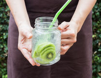 Hand on serving glass of iced kiwi soda drink Stock Images
