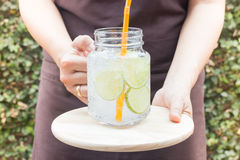 Hand on serving glass of iced lime soda drink Stock Images