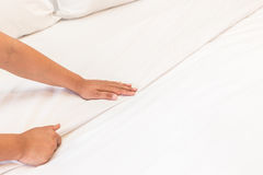 Hand set up white bed sheet in hotel room Royalty Free Stock Photos