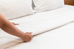 Hand set up white bed sheet in hotel room Royalty Free Stock Photo