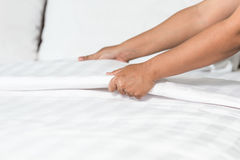 Hand set up white bed sheet in hotel room Stock Photos