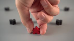 A hand sets a red figure surrounded by black figures on a gray surface. Team Leader Concept stock video footage