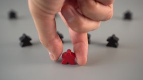 A hand sets a red figure surrounded by black figures on a gray surface. Team Leader Concept stock video