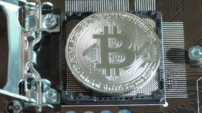 Hand sets Silver Bitcoin virtual currency on a motherboard instead cpu. New metal cryptocurrency bitcoin on the circuit stock video