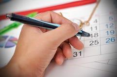 Hand setzt ein Kennzeichen auf Kalender Stockfotos