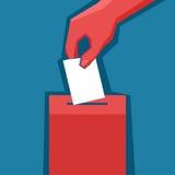 Hand setzt Stimmzettel in die Wahlurne ein Stockbild