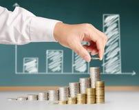 Hand setzte Münze zum Geld Lizenzfreie Stockfotos