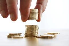 Hand setzte Münze zum Geldstapel auf weißen Hintergrund Nahaufnahme der Hand eine Münze zum Stapel Münzen setzend Geschäftsfinanz Stockfotos