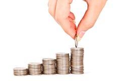 Hand setzte Münze zum Geldtreppenhaus Stockfoto