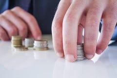 Hand setzte Münze zum Stapel Lizenzfreie Stockfotografie