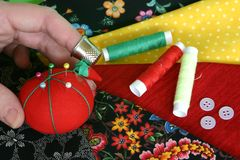 Hand Sewing. Hand with thimble reaching for pin cushion with fabric, cotton and buttons in background Stock Photos