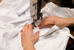 Hand sewing. She sews on the old sewing machine Stock Photo