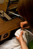 Hand sewing. She sews on the old sewing machine Royalty Free Stock Photos