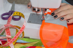 Hand on sewing machine.Dressmaker work on the sewing machine. Hobby sewing fabric as a small business concept. sewing machine and Stock Photo