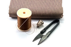 Hand sewing tools. Thimble,needle,spools and scissor with cloth for sewing on white background Stock Photo
