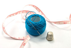 Hand sewing tools. Thimble, needles and blue thread ball  for sewing on white background Stock Image
