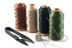 Hand sewing tools. Thimble, needles, spools and scissors for sewing on a background thread Stock Photos