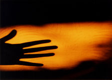 Hand shadow. Shadow of an hand on a wall during sunset Royalty Free Stock Photo