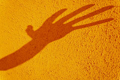 Hand shadow distorted on texturized yellow wall Stock Photo