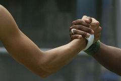 Hand shake 01. Hands shake with two hands wearing wrist bands Royalty Free Stock Photography