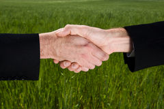 Hand Shake. Business hand shake with green field in background Royalty Free Stock Images