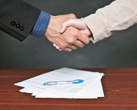 Hand shake. Business deal between client and business man with the signed documents on the table Royalty Free Stock Photo
