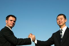 Hand shake 6. 2 businessmen shakking hands with the blue sky behind them Stock Image