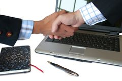 Hand shake. Near a laptop royalty free stock photos