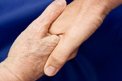 Hand shake against a blue background Royalty Free Stock Images
