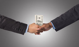 Hand shake between a businessman with dollar money on dark blue Royalty Free Stock Photography