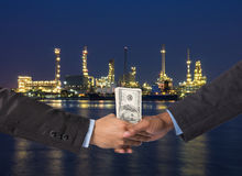 Hand shake between a businessman with dollar money on Petrochemi Stock Photography