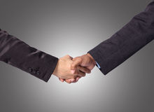 Hand shake between a businessman on gray background Stock Images