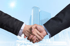 Hand shake between a businessman on Modern business building gla Royalty Free Stock Images