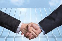 Hand shake between a businessman on Modern glass building backgr Stock Image