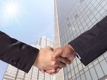 Hand shake between a businessman on Modern glass building backgr Royalty Free Stock Photo