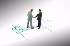 Hand shake and contract. Two businessman closing a deal shaking hands Stock Images